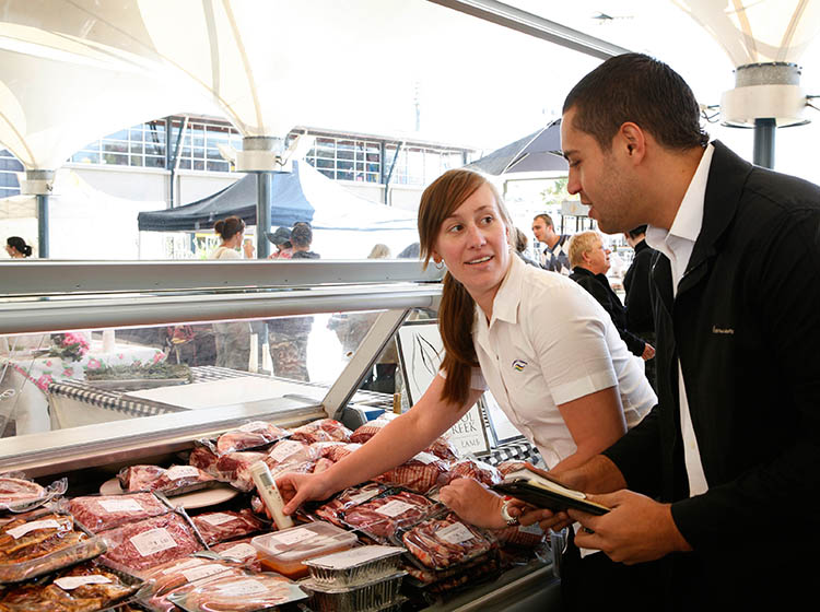 A food inspector in a black suit with a female staff member in a white uniform taking the temperature of a butchers meat counter.