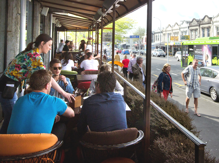 People eat at the Ponsonby Produce Market in Auckland as pedestrians walk by; Sheep and cattle graze on a lush New Zealand farm; Breakfast of toast, eggs, beans and a coffee is served on a table with a NZ mountain range in the background.